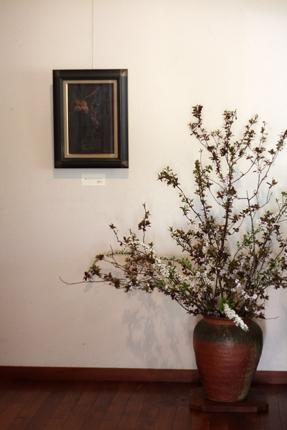ベニスモモにユキヤナギ 壁の絵は四竈公子『たべそこなったぶどう』(2000年 油彩)