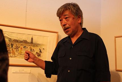 小林豊さん 絵本『とうさんとぼくと風のたび』(ポプラ社 2012)の原画の前で