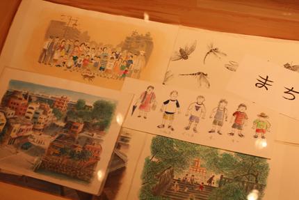 絵本『まち ーぼくたちのいちにち』の原画を木製のケースに平置きというラフなかたちでご覧いただけるように展示しました