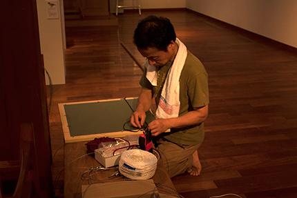 展示作業進行中その1 額を整える鈴木まもるさん