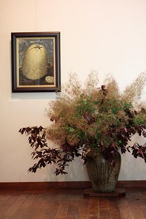 スモークツリーにベニスモモの葉。壁面の作品は『花梨』(渡辺隆次 アクリル等 1992年)