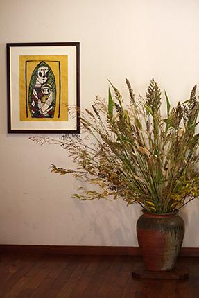 キビなど雑穀を中心に活けていただきました。壁面の作品は『聖母子』(渡辺禎雄 型染版画 1991)です