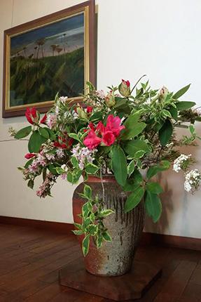 シャクナゲの花を中心にハコネウツギやコデマリをあしらいました。壁面の作品は『北国の晩夏(3)』(四竈公子 2013年 油彩)です